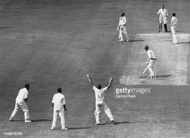 Jim Parks, wicketkeeper for England raises his arms in celebration after catching Peter Lashley of the West Indies off a delivery by John Snow for 49...