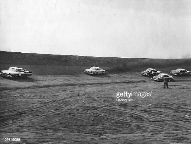 Jim Paschal in a Mercury leads the Ford of Paul Goldsmith the Chevrolet of Jack Smith and the Ford of Ralph Moody during a NASCAR Cup race at...