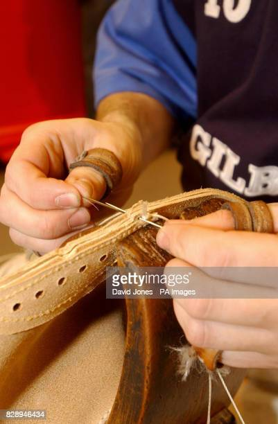 Jim Pritchard sits astride a 'horse' as he uses waxed thread to sew together the panels of a traditional match rugby ball in much the same way as the...