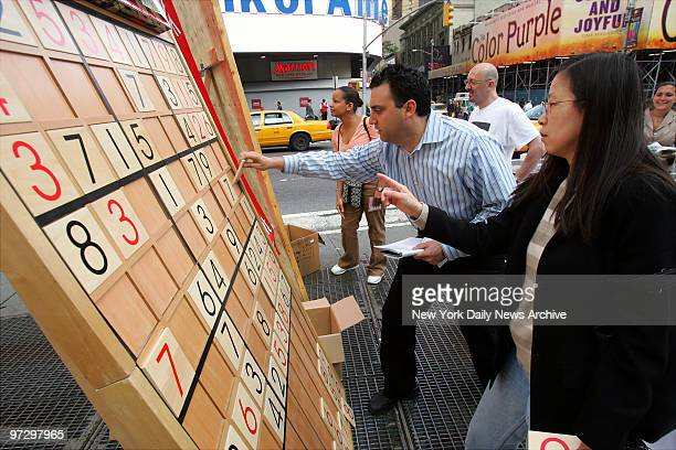 Jim Ressler owner of Sudoku Board USA helps Dorris Lam of Glen Rock NJ solve a Sudoku puzzle on a gigantic board in Times Square during a nationwide...