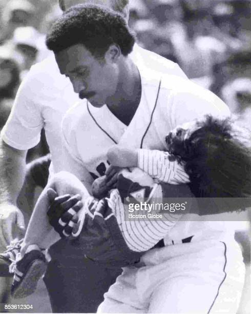 Jim Rice carries 4yearold Jonathan Keane into the Red Sox dugout after he was struck and injured by Dave Stapleton's line drive during a game against...