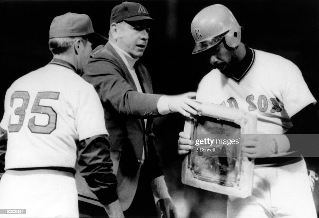 Jim Rice #14 of the Boston Red Sox is given the first base bag from umpire George Maloney after being the first player in 19 years to reach 400 total bases in one season during the game against the Toronto Blue Jays on September 29, 1978 at Fenway Park in Boston, Massachusetts. First base coach Johnny Pesky #35 of the Red Sox looks on.