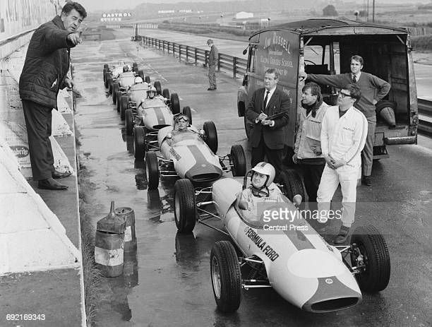 Jim Russell International Racing School instructor Jim Russell gives out instruction to his pupil drivers sitting aboard their Lotus 51 Formula Ford...