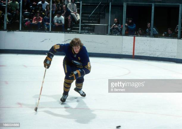 Jim Schoenfeld of the Buffalo Sabres goes for the puck during an NHL game against the California Golden Seals circa 1976 at the Oakland Coliseum in...
