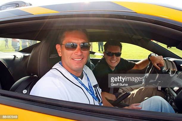 Jim Schwartz Head Coach of the National Football League's Detroit Lions rides in the pace car with a guest prior to the start of the NASCAR Sprint...