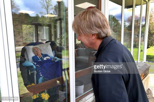 Jim Siteman talks to his 98yearold mother Anna Siteman through an opening in a window at the DaggettCrandallNewcomb Home in Norton MA on May 9 2020...