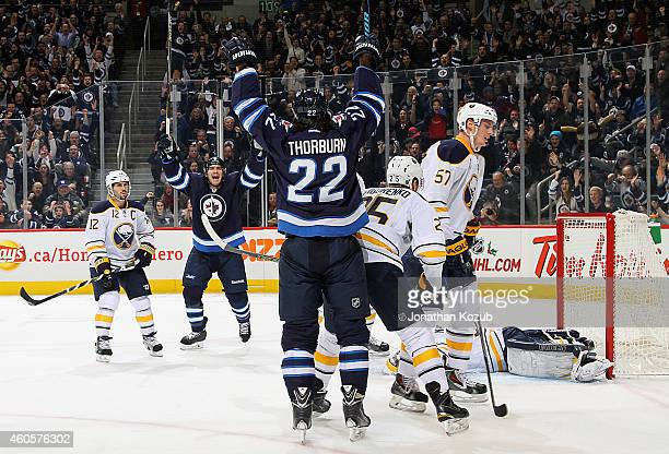 Jim Slater and Chris Thorburn of the Winnipeg Jets raise their arms in celebration after Thorburn scored a third period goal against the Buffalo...
