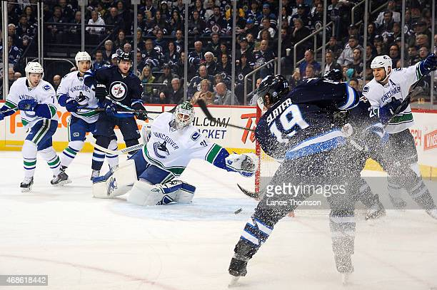 Jim Slater of the Winnipeg Jets shoots the puck past a diving Eddie Lack of the Vancouver Canucks for a first period goal on April 4 2015 at the MTS...