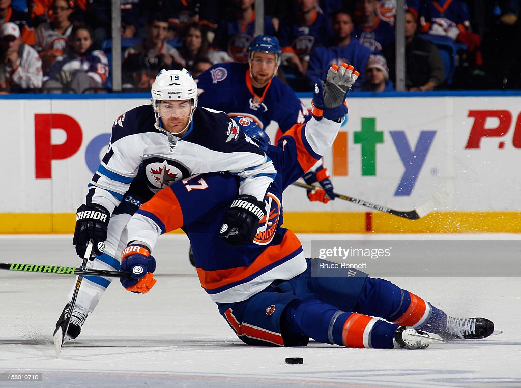 Jim Slater #19 of the Winnipeg Jets takes a holding penalty as Matt Martin #17 of the New York Islanders takes a penalty for embellishment during the second period at the Nassau Veterans Memorial Coliseum on October 28, 2014 in Uniondale, New York.