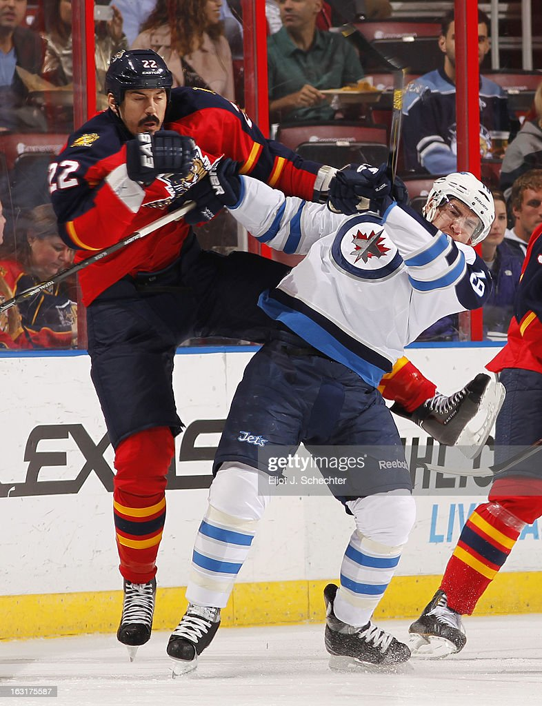 Jim Slater #19 of the Winnipeg Jets tangles with George Parros #22 of the Florida Panthers at the BB&T Center on March 5, 2013 in Sunrise, Florida.