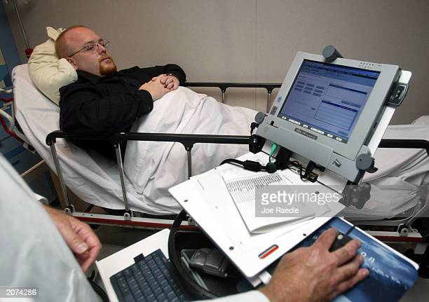Jim Smith lies on a hospital bed during a demonstration of the wireless Carecast health information system June 11 2003 in Hollywood Florida IDX a...