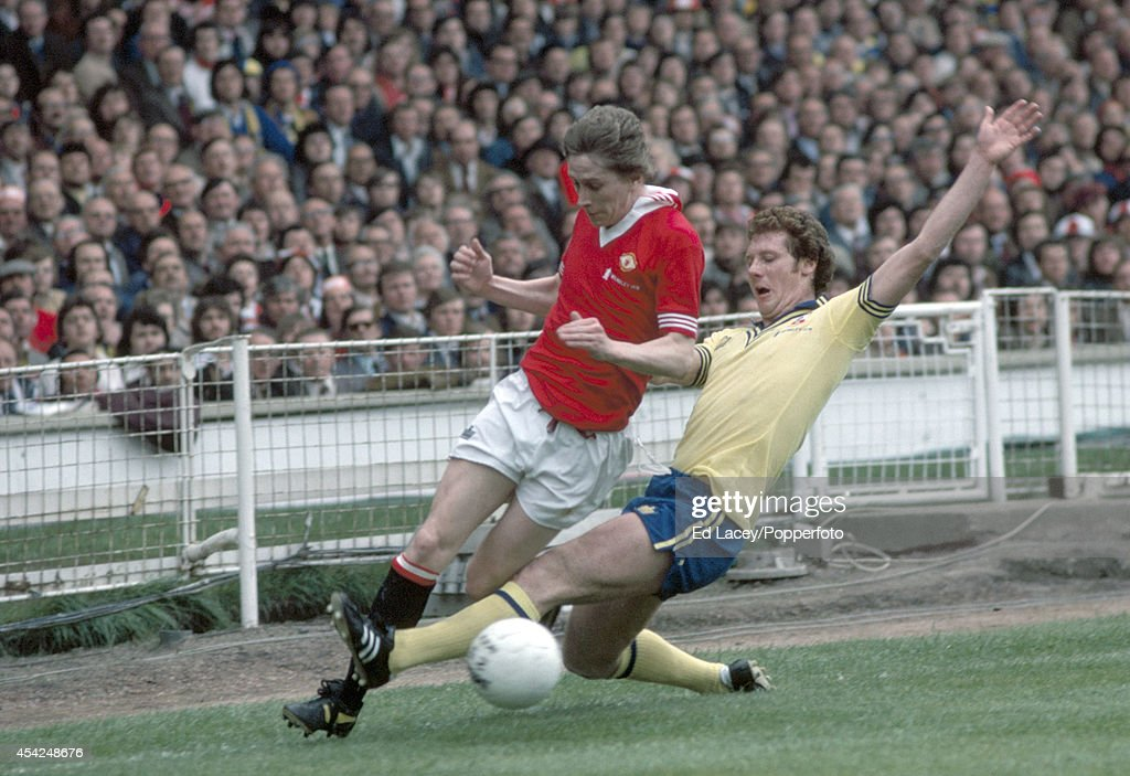 Jim Steele of Southampton (right) slides in to tackle Gerry Daly of Manchester United during the FA Cup Final at Wembley Stadium in London on 1st May 1976. Southampton won 1-0.