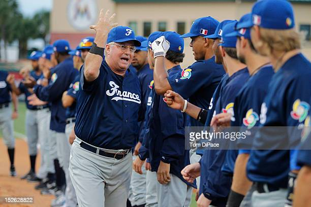 Jim Stoeckel manager of Team France is greeted by players on the base path during the opening ceremony before game 2 of the Qualifying Round of the...
