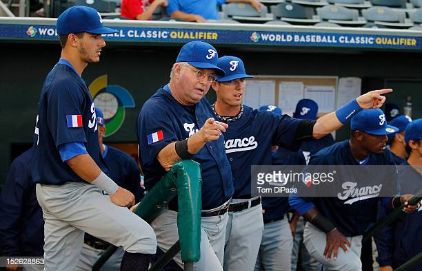 Jim Stoeckel manager of Team France talks to Emmanuel Garcia of Team France in the dugout before game 2 of the Qualifying Round of the 2013 World...