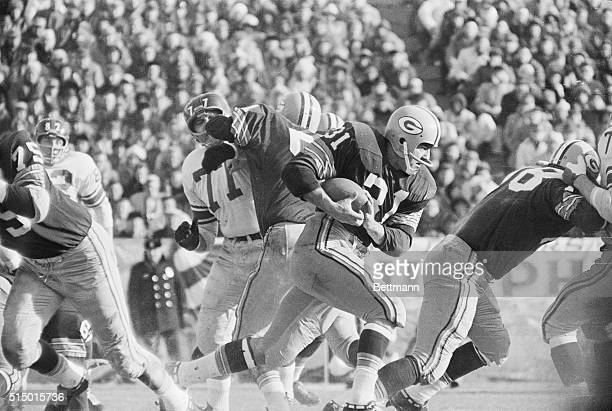 Jim Taylor of Green Bay goes through the line for 7 yards against the New York Giants during the NFL Pro Championship game in this photograph The...