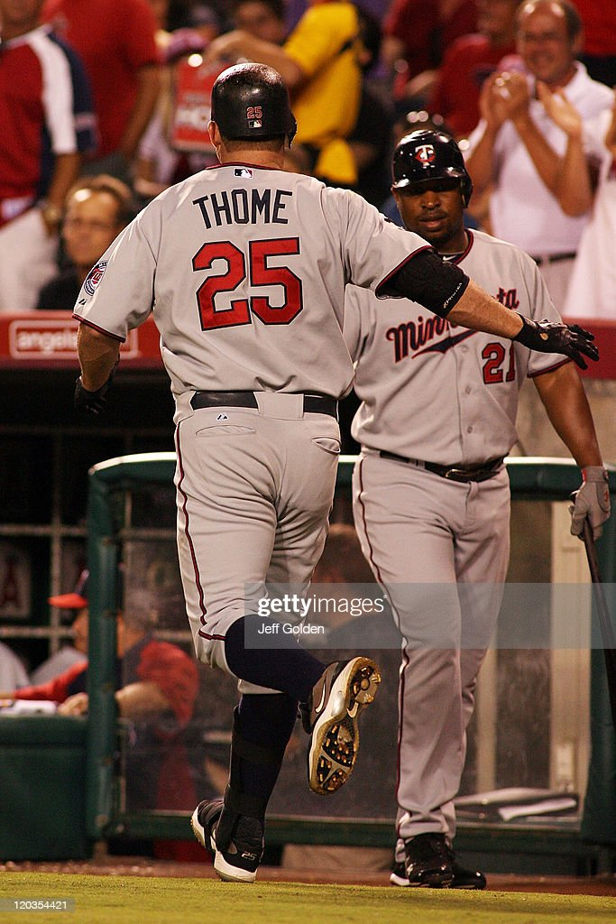 Jim Thome #25 of the Minnesota Twins is congratulated after hitting a home run against the Los Angeles Angels of Anaheim in the eighth inning of the game at Angel Stadium of Anaheim on August 4, 2011 in Anaheim, California. Thome's home run was the 598th of his career.