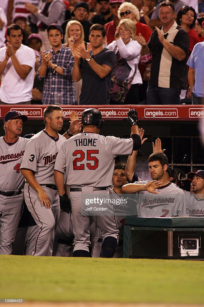 Jim Thome #25 of the Minnesota Twins is congratulated by teammates as he returns to the dugout after hitting a home run against the Los Angeles Angels of Anaheim in the eighth inning of the game at Angel Stadium of Anaheim on August 4, 2011 in Anaheim, California. Thome's home run was the 598th of his career.