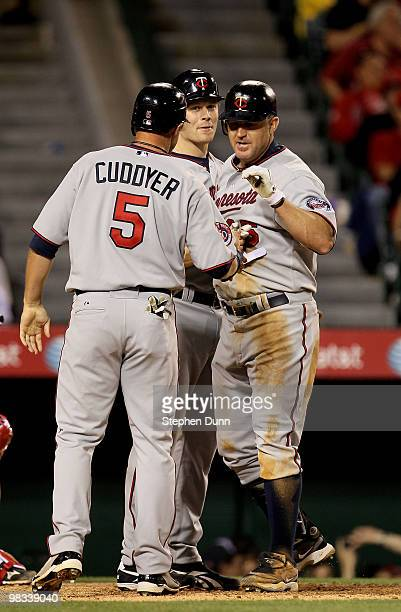Jim Thome of the Minnesota Twins is greeted by Michael Cuddyer and Justin Morneau after they all score on Thome's three run home run in the eighth...