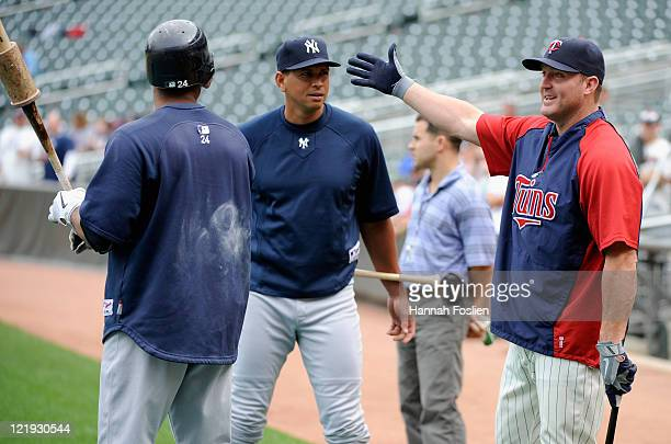 Jim Thome of the Minnesota Twins speaks with Robinson Cano and Alex Rodriguez of the New York Yankees during batting practice before their game on...