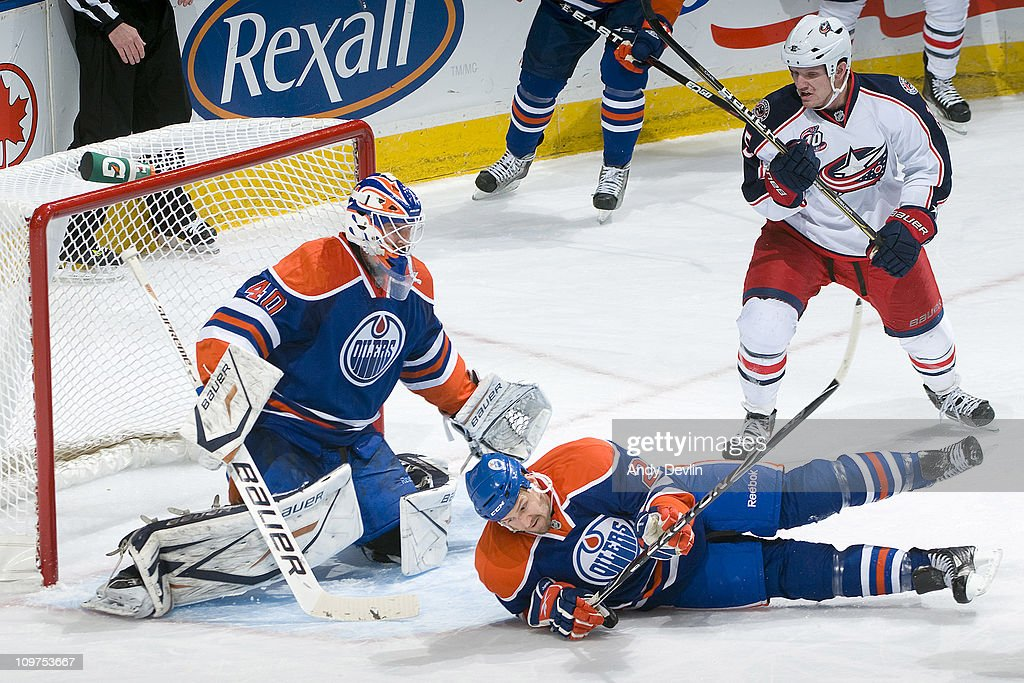 Jim Vandermeer #2 and Devan Dubnyk #40 of the Edmonton Oilers collapse in the crease to defend their net against the Columbus Blue Jackets Rexall Place on March 3, 2011 in Edmonton, Alberta, Canada.