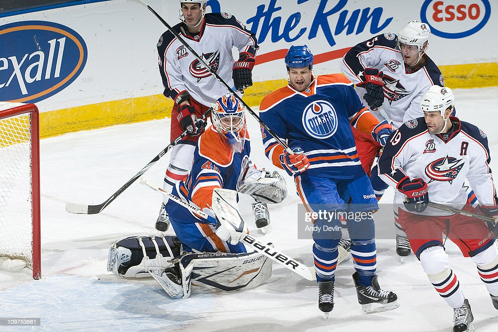 Jim Vandermeer #2 of the Edmonton Oilers tries to clear the front of the net while Ethan Moreau #19 of the Columbus Blue Jackets pressures the crease at Rexall Place on March 3, 2011 in Edmonton, Alberta, Canada.