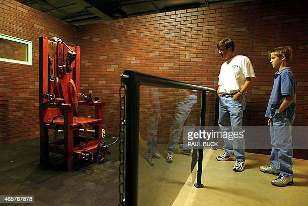 Jim Wilde and his son Wilson view the electric chair nicknamed 'Old Sparky' on display at the Texas Prison Museum in Huntsville Texas 07 December...