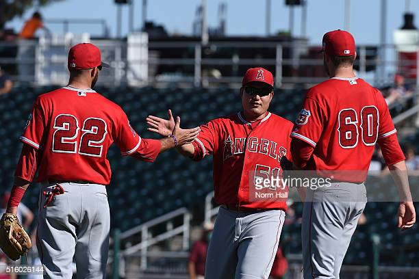 JiMan Choi of the Los Angeles Angels of Anaheim celebrates with teammates Kaleb Cowart and AJ Achter after a 63 win against the Cleveland Indians of...