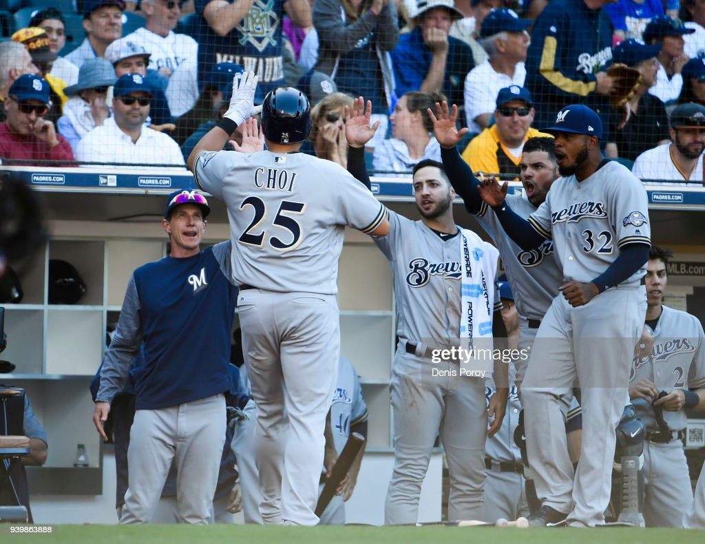 Ji-Man Choi #25 of the Milwaukee Brewers in congratulated after scoring during the twelfth inning on Opening Day against the San Diego Padres at PETCO Park on March 29, 2018 in San Diego, California.