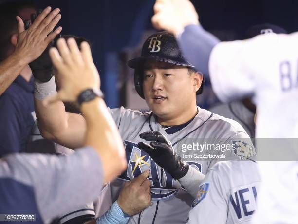 JiMan Choi of the Tampa Bay Rays is congratulated by teammates in the dugout after scoring a run in the seventh inning during MLB game action against...