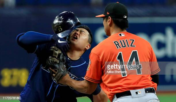 Ji-Man Choi of the Tampa Bay Rays is tagged in the face by Rio Ruiz of the Baltimore Orioles on a triple in the seventh inning during game two of a...