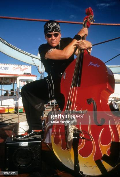 Jimbo Wallace of the rockabilly band 'Reverend Horton Heat' stands with his flameemblazoned upright bass during a lull at the 'Warped Tour' April...