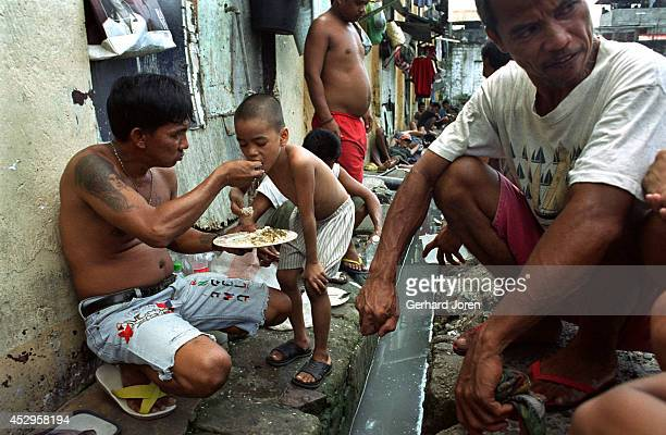 Jim-Boy has lunch with a friend amidst the slum-like conditions of Manila City Jail. Just 6 years old, Jim-Boy lives with his father in his cell in...