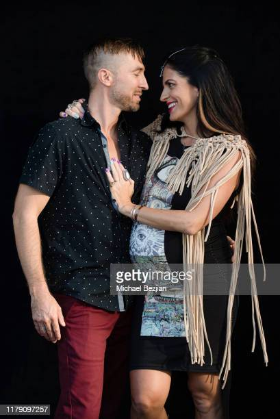 Jimi Merk and Bridgetta Tomarchio wear jewelry by Jimeye Designs and clothing by Gary Allen Designs during the Giveback Day at TAP The Artists...