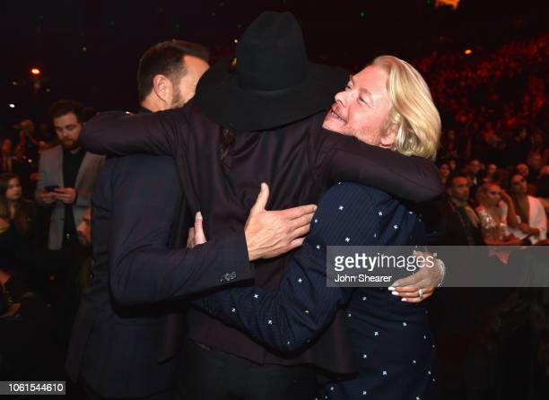 Jimi Westbrook and Philip Sweet of Little Big Town hug Cameron Duddy of Midland during the 52nd annual CMA Awards at the Bridgestone Arena on...