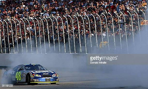 Jimie Johnson driver of the Lowe's Chevrolet Monte Carlo smokes his tires as he celebrates his win during the Carolina Dodge Dealers 400 at the...