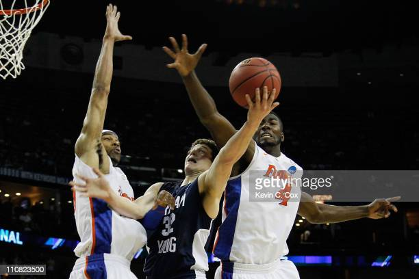 Jimmer Fredette of the Brigham Young Cougars goes up for a shot between Alex Tyus and Patric Young of the Florida Gators during the Southeast...