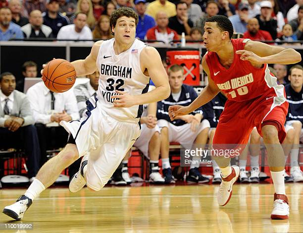 Jimmer Fredette of the Brigham Young University Cougars drives against Kendall Williams of the New Mexico Lobos during a semifinal game of the Conoco...