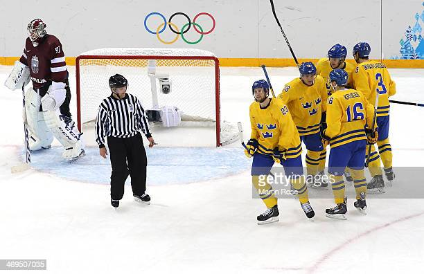 Jimmie Ericsson of Sweden celebrates with teammates after scoring against Kristers Gudlevskis of Latvia in the second period during the Men's Ice...