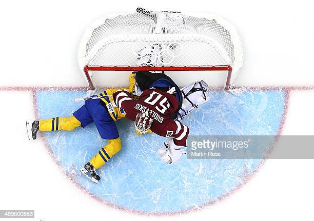 Jimmie Ericsson of Sweden slides into the net against Kristers Gudlevskis of Latvia in the first period during the Men's Ice Hockey Preliminary Round...