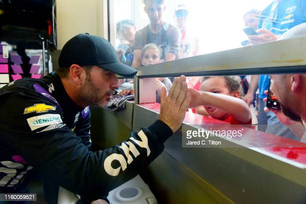 Jimmie Johnson driver of the Ally Chevrolet signs autographs for fans in the garage area during practice for the Monster Energy NASCAR Cup Series...