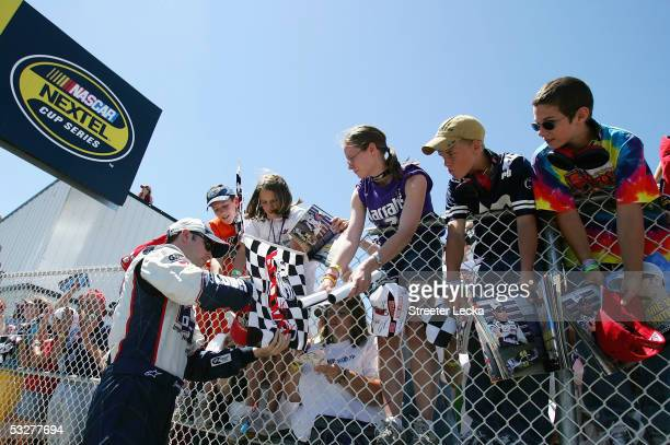 Jimmie Johnson, driver of the Hendrick Motorsports Lowe's Chevrolet, signs autographs during the NASCAR Nextel Cup Pennsylvania 500 qualifying on...