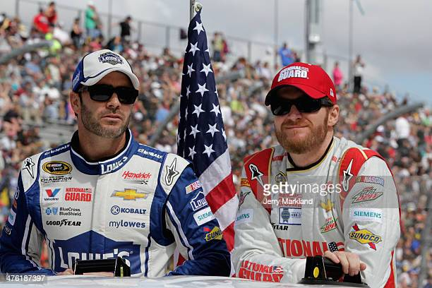 Jimmie Johnson driver of the Lowe's Chevrolet and Dale Earnhardt Jr driver of the National Guard Chevrolet take part in prerace ceremonies during the...