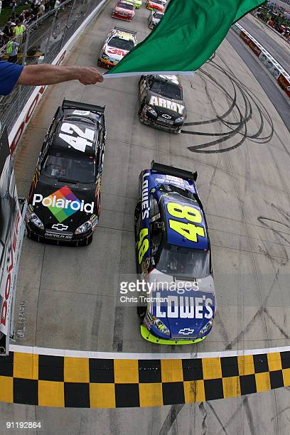 Jimmie Johnson driver of the Lowe's Chevrolet and Juan Pablo Montoya driver of the Polaroid Chevrolet lead the field at the start of the NASCAR...