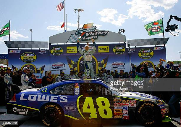 Jimmie Johnson, driver of the Lowe's Chevrolet, celebrates as he stands on his car in victory lane after winning the NASCAR Nextel Cup Series Jim...