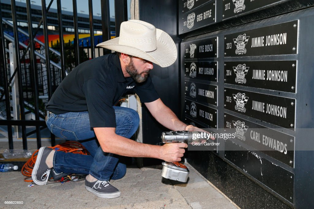 Jimmie Johnson, driver of the #48 Lowe's Chevrolet, celebrates by drilling his nameplate into the Wall of Champions after winning the Monster Energy NASCAR Cup Series O'Reilly Auto Parts 500 at Texas Motor Speedway on April 9, 2017 in Fort Worth, Texas.