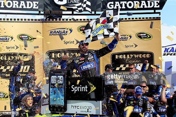 Jimmie Johnson driver of the Lowe's Chevrolet celebrates in Victory Lane after winning the NASCAR Sprint Cup Series Hollywood Casino 400 at Kansas...