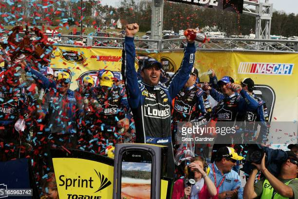 Jimmie Johnson driver of the Lowe's Chevrolet celebrates in Victory Lane after winning the NASCAR Sprint Cup Series STP Gas Booster 500 on April 7...