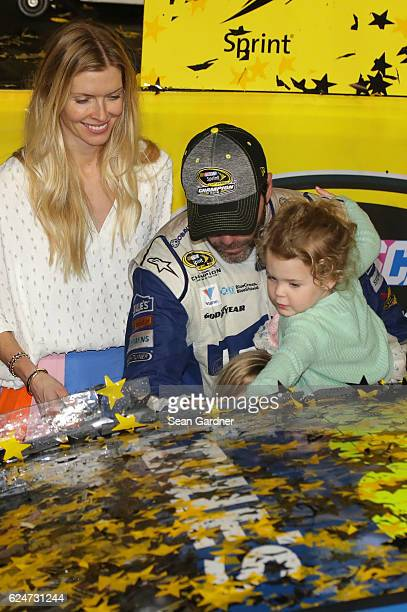 Jimmie Johnson driver of the Lowe's Chevrolet celebrates in Victory Lane with his wife Chandra and daughters Genevieve Marie and Lydia Norriss after...
