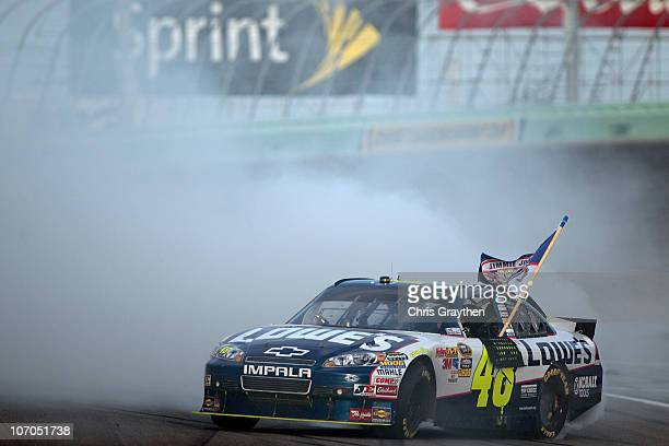 Jimmie Johnson driver of the Lowe's Chevrolet celebrates with a burnout after finishing in second place in the Ford 400 to clinch a fifth consecutive...