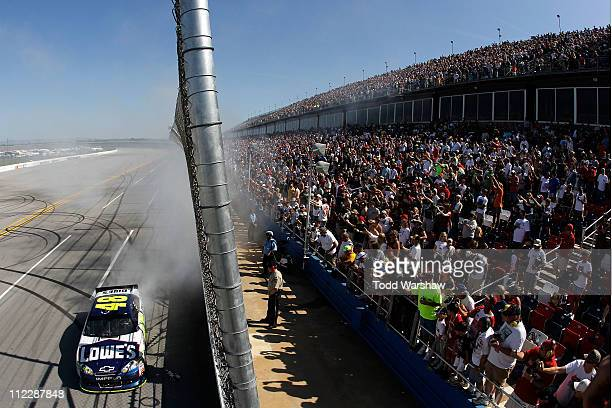 Jimmie Johnson driver of the Lowe's Chevrolet celebrates with a burnout after winning the NASCAR Sprint Cup Series Aaron's 499 at Talladega...